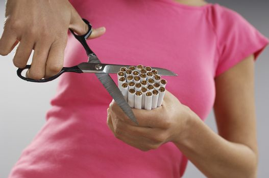 Midsection of an African American woman cutting bundle of cigarettes