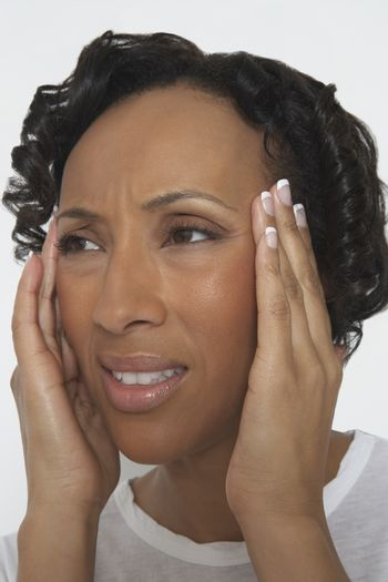 Closeup of an African American woman suffering from severe headache isolated over white background