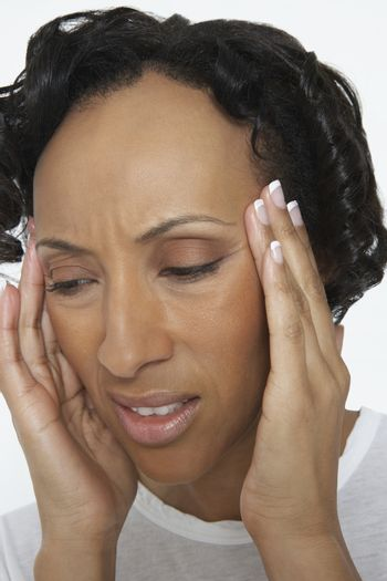 Closeup of unhappy African American woman suffering from severe headache isolated over white background