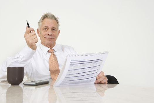 Senior businessman with paperwork at office desk