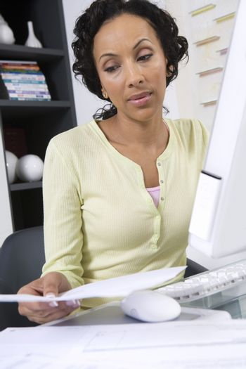 Businesswoman with paperwork using computer