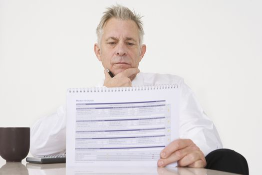 Portrait of a serious senior businessman reading official document at office desk
