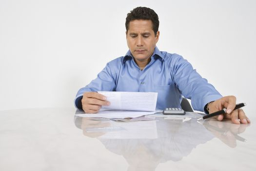 Serious businessman doing finances at desk