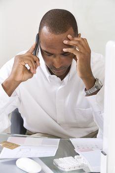 Tensed businessman paying bills through credit card