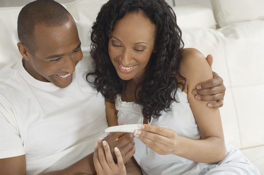 An African American couple happy with the pregnancy test results