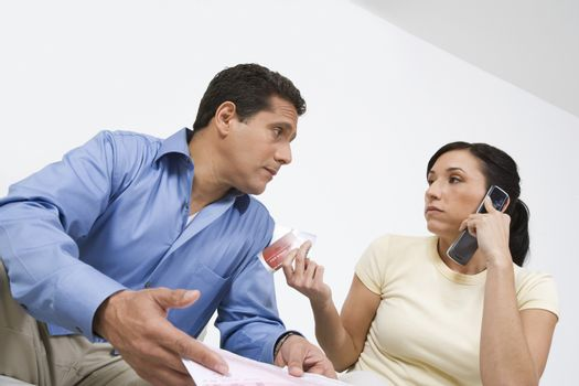 Worried man with credit card bills looking at woman on call