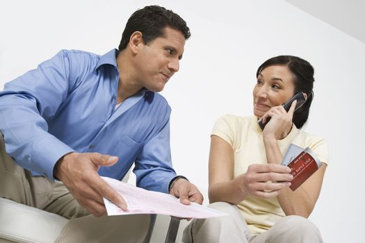 Woman with credit cards on call looking at man holding bill