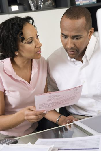 An African American couple worried over excess domestic bill