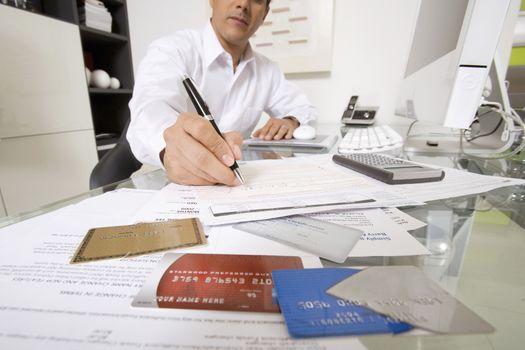 Businessman filling credit card forms at desk