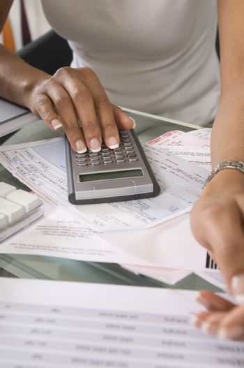 Midsection of a woman calculating budget at home