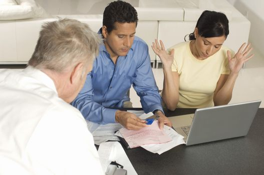 Couple calculating financial budget with advisor at home