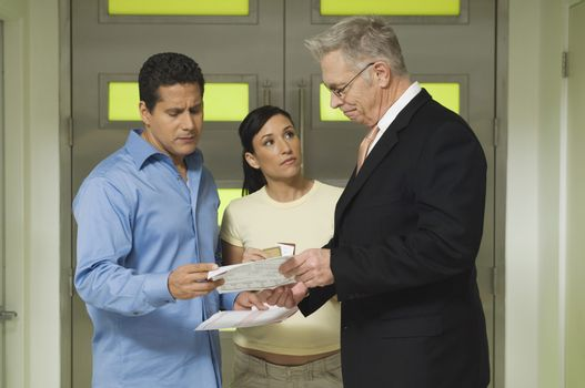 Couple and senior businessman with documents in office