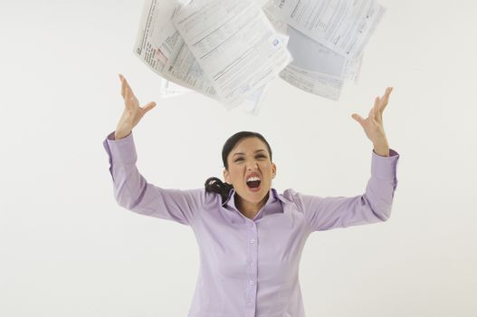 Irritated businesswoman tossing bills isolated over white background