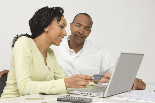 Happy African American couple making an online transaction