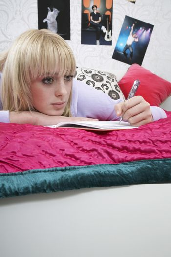 Thoughtful teenage student writing in book while lying on bed
