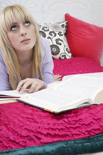Thoughtful teenage girl with books lying in bed