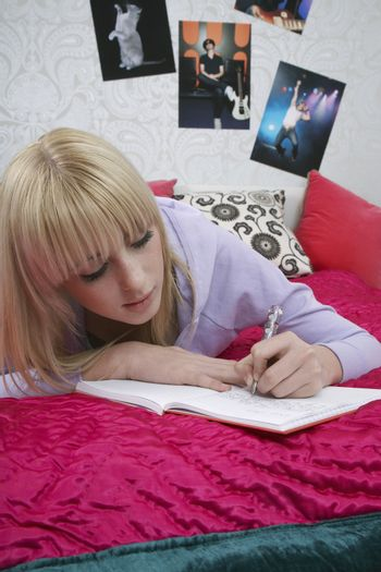 Young female student writing in book on bed