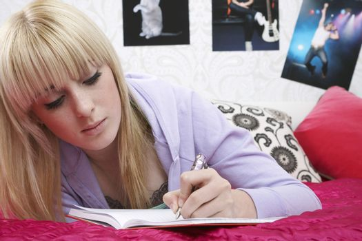 Beautiful young female student writing in book on bed