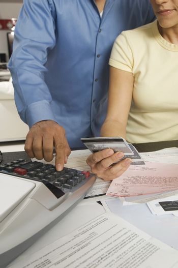 Midsection of couple calculating financial budget on desktop calculator