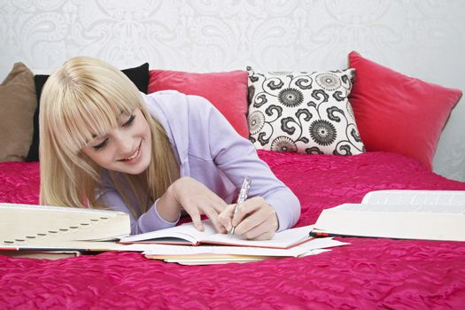 Beautiful teenage student writing in book while smiling on bed