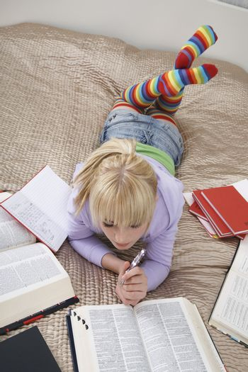 Full length of young female student reading in bed