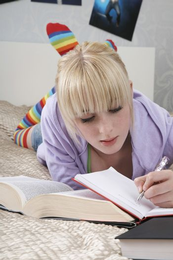 Full length of young female student writing in book while lying on bed