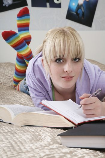 Full length portrait of beautiful female student writing in book while lying on bed