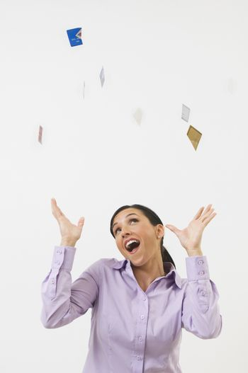 Happy beautiful woman tossing credit cards in the air isolated over white background