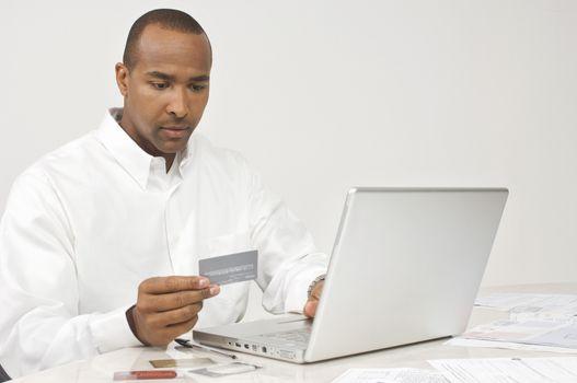 Businessman making online transaction while using credit card