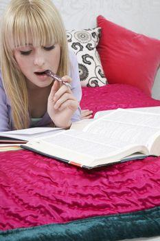 Beautiful teenage girl studying in bed
