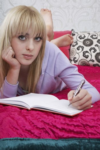 Portrait of beautiful teenage girl writing in book on bed