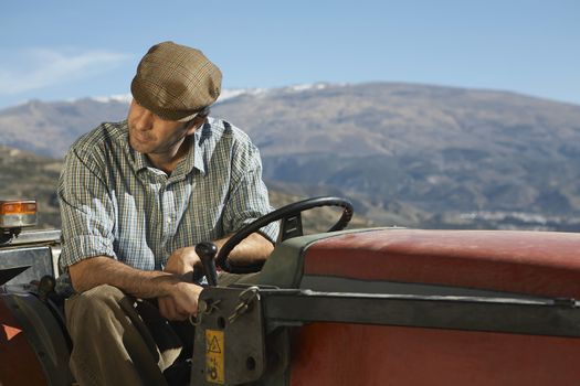 Middle age farmer sitting on tractor against mountain