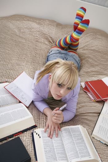 Full length of thoughtful young female student learning in bed