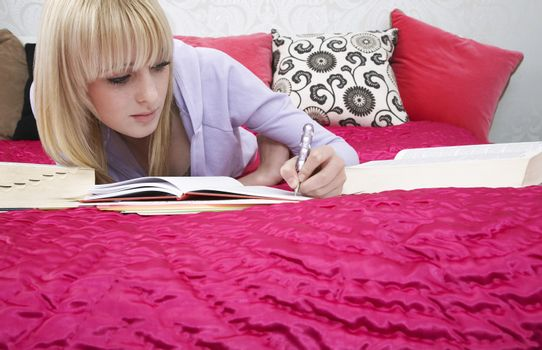 Full length of beautiful teenage student writing in book while lying on bed