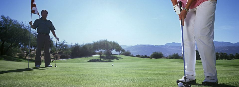 Woman playing golf low section
