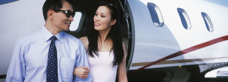 Couple exiting private plane