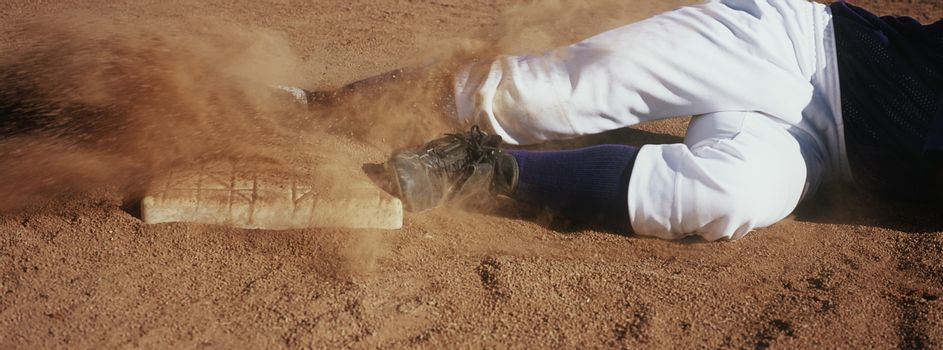 Low section of baseball player sliding towards base on field