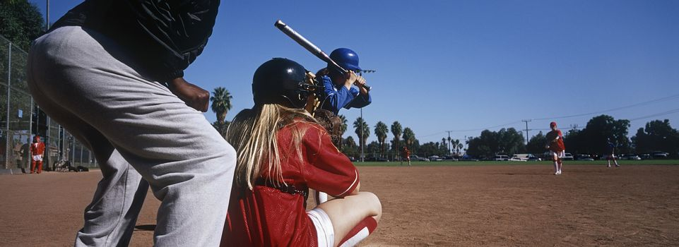 Professional female baseball team practicing on ground with umpire