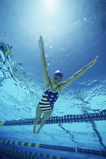 Female swimmer wearing United States swimsuit while swimming in pool