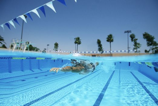 Young professional swimmer practicing in pool