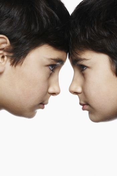 Twin boys (13-15) head to head close-up