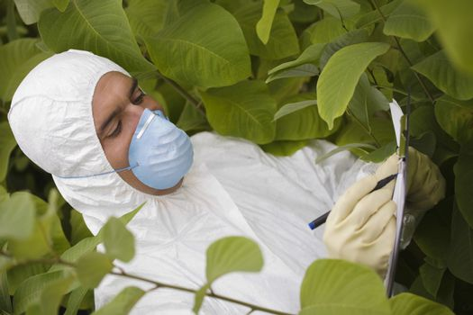 Worker in protective mask and suit writing on clipboard amongst plants