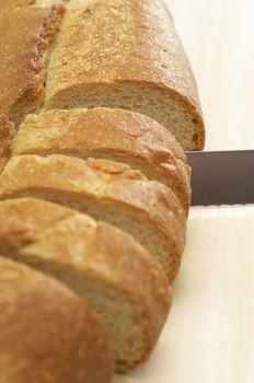 Closeup of a knife slicing baguette