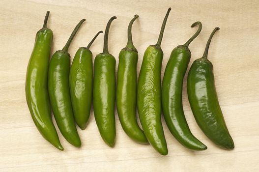 Closeup of green chili peppers in row on chopping board