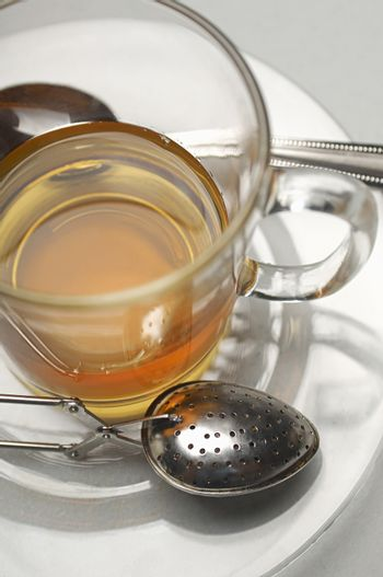Closeup of tea cup with strainer and spoon in saucer over grey background