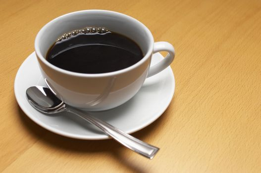 Isolated coffee cup with spoon in saucer on wooden surface