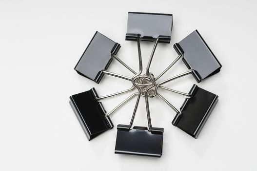 Closeup of black binder clips forming circle over white background