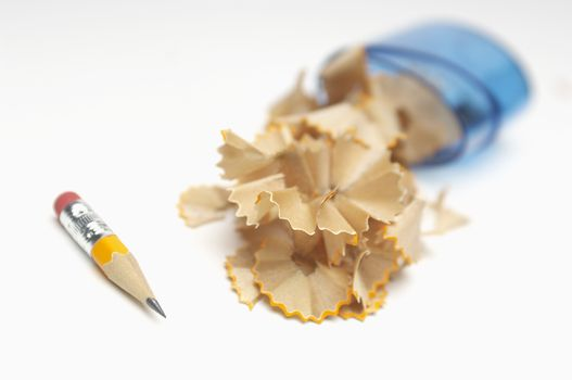 Closeup of sharpened pencil with shavings over white background