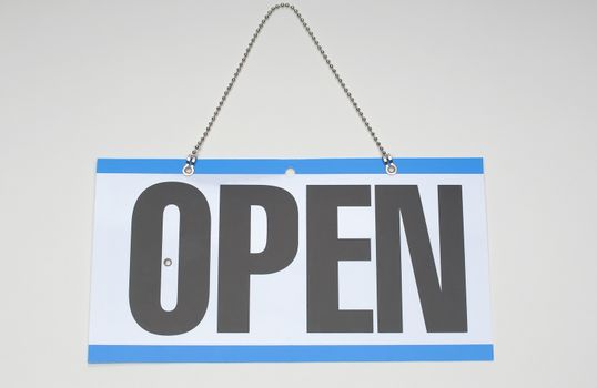 """Closeup of signboard with """"Open"""" sign over white background"""