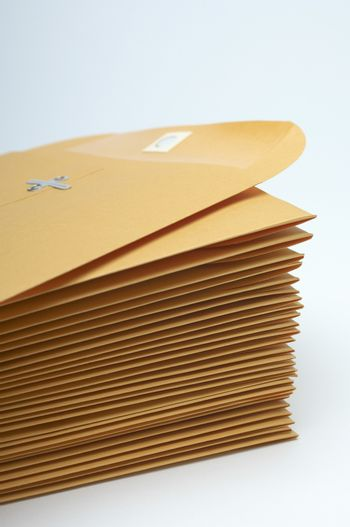 Stack of brown envelopes with clipping isolated over white background